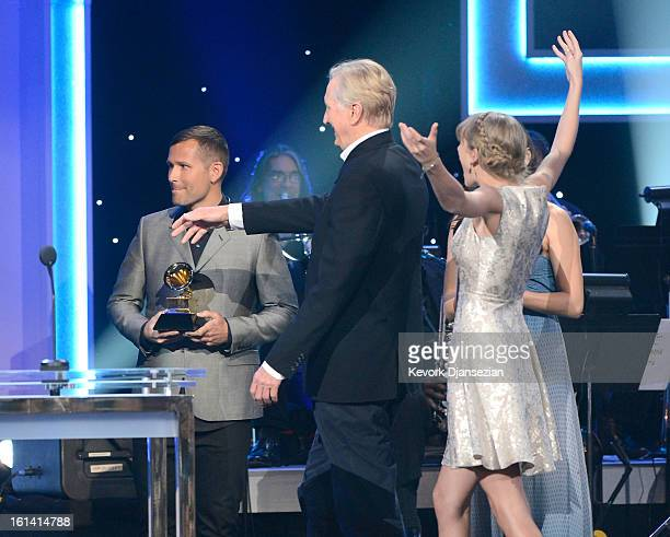 Musician T Bone Burnett and singer Taylor Swift walk onstage to accept the Best Song Written For Visual Media Award for 'Safe Sound ' onstage at the...