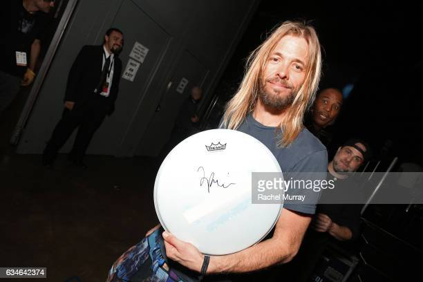 Musician Taylor Hawkins of the Foo Fighters poses with the charity signings at MusiCares Person of the Year honoring Tom Petty during the 59th GRAMMY...