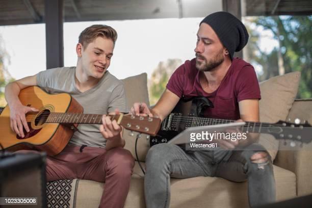 musician teaching student how to play guitar - ギタリスト ストックフォトと画像