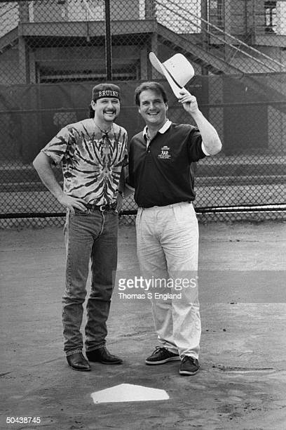 CW musician Tim McGraw w father former baseball player Tug McGraw as they pose sporting each other's signature hats while standing on baseball field