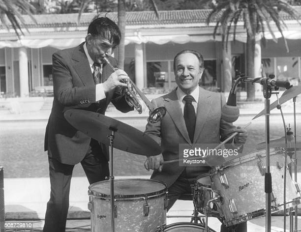 Musician Tino Rossi plays the drums, accompanied by Aime Barelli on the trumpet next to a swimming pool in Monaco, circa 1955.
