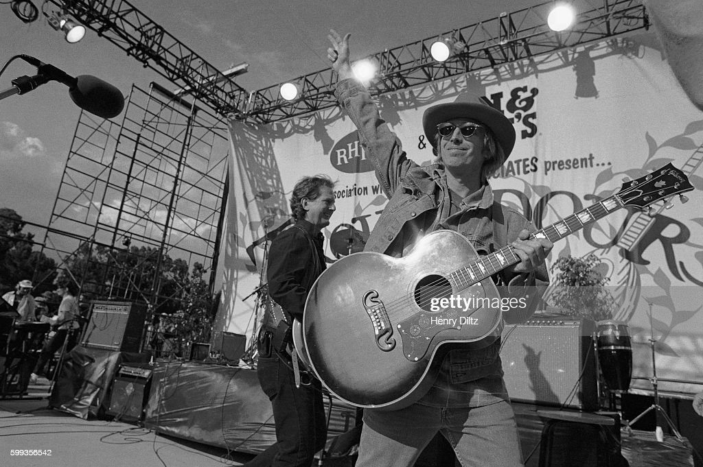 Musician Tom Petty waves to the crowd during his performance at the Troubadours of Folk Festival on the UCLA campus. Roger McGuinn is behind him, to the left.