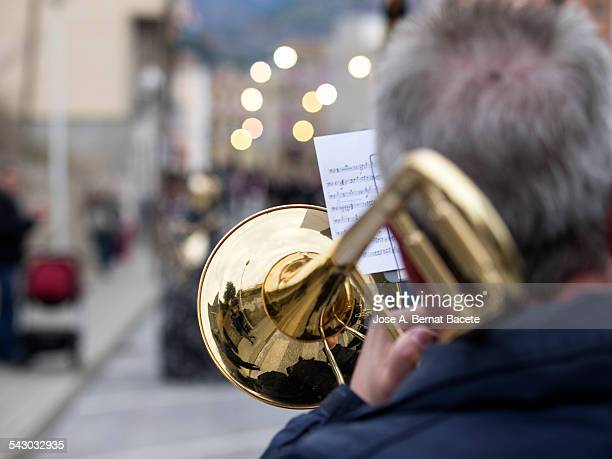 Musician touching a trombonist in a parade