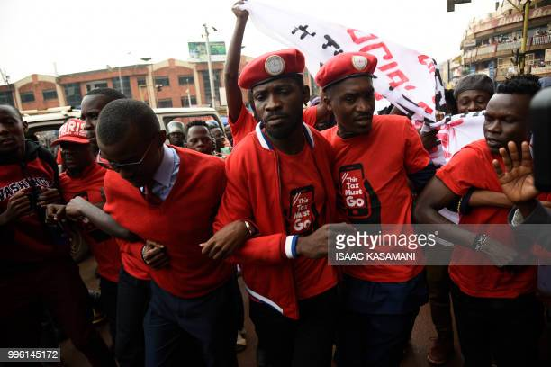 Musician turned politician Robert Kyagulanyi is joined by other activists in Kampala on July 11 2018 in Kampala during a demonstration to protest a...