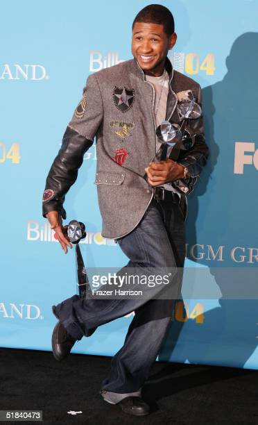 Musician Usher poses backstage with his awards at the 2004 Billboard Music Awards at the MGM Grand Garden Arena on December 8 2004 in Las Vegas...