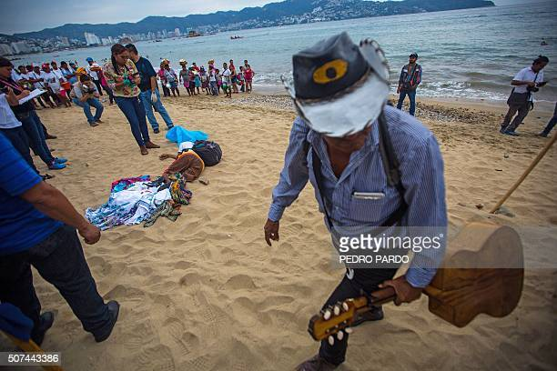 A musician walks past forensic workers as they surround the body of a murdered man at Hornos beach in the tourist city of Acapulco Guerrero state...