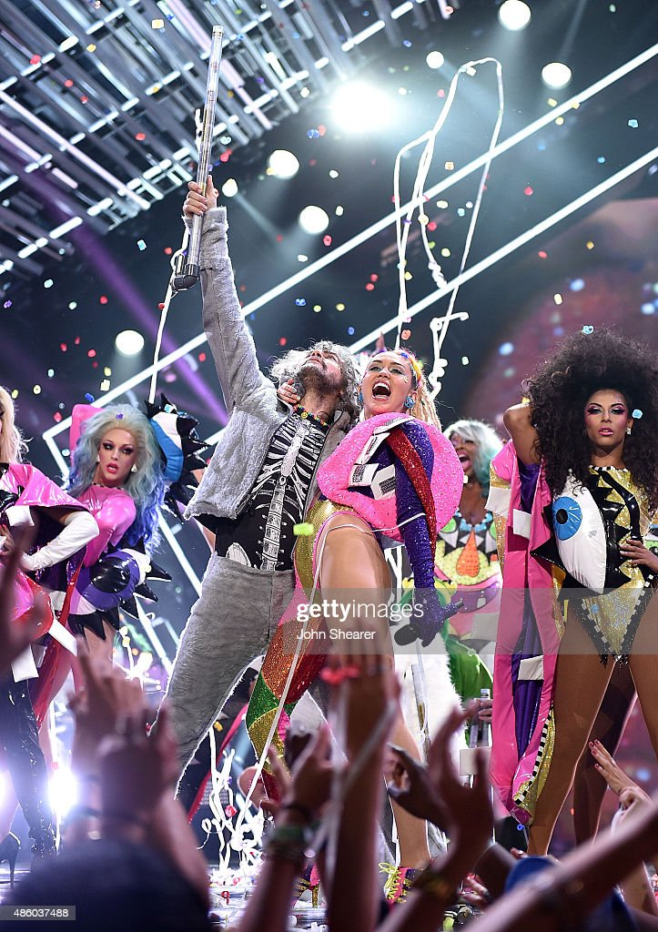 Musician Wayne Coyne of The Flaming Lips (L) and host Miley Cyrus, styled by Simone Harouche, performs onstage during the 2015 MTV Video Music Awards at Microsoft Theater on August 30, 2015 in Los Angeles, California.