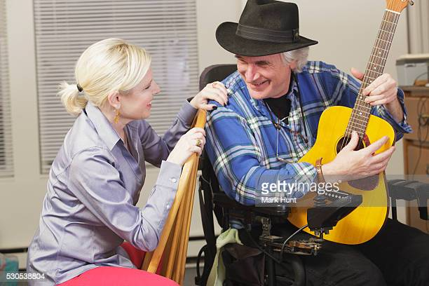 musician with multiple sclerosis in a motorized wheelchair with his guitar playing for a friend - multiple sclerosis stock photos and pictures