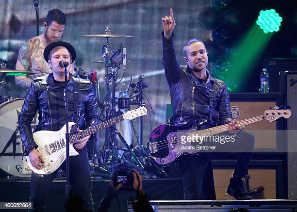 Musicians Andy Hurley Patrick Stump and Pete Wentz of Fall Out Boy perform onstage during 1035 KISS FM's Jingle Ball 2014 at Allstate Arena on...