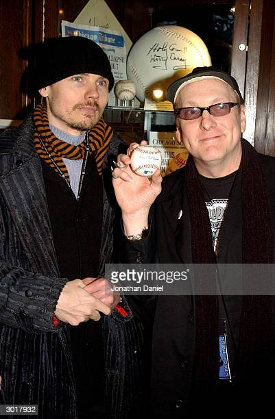 Musicians Billy Corgan and Rick Nielson pose with the cursed Chicago Cubs baseball before it was destroyed on February 26 2004 at Harry Caray's...