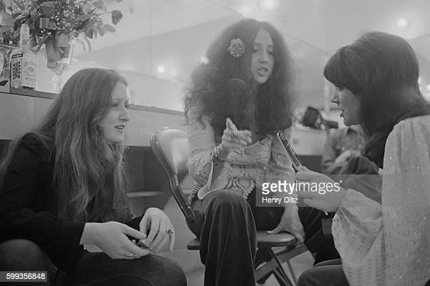 Musicians Bonnie Raitt Maria Muldaur and Linda Ronstadt talk in their dressing room before performing at the Santa Monica Civic Auditorium
