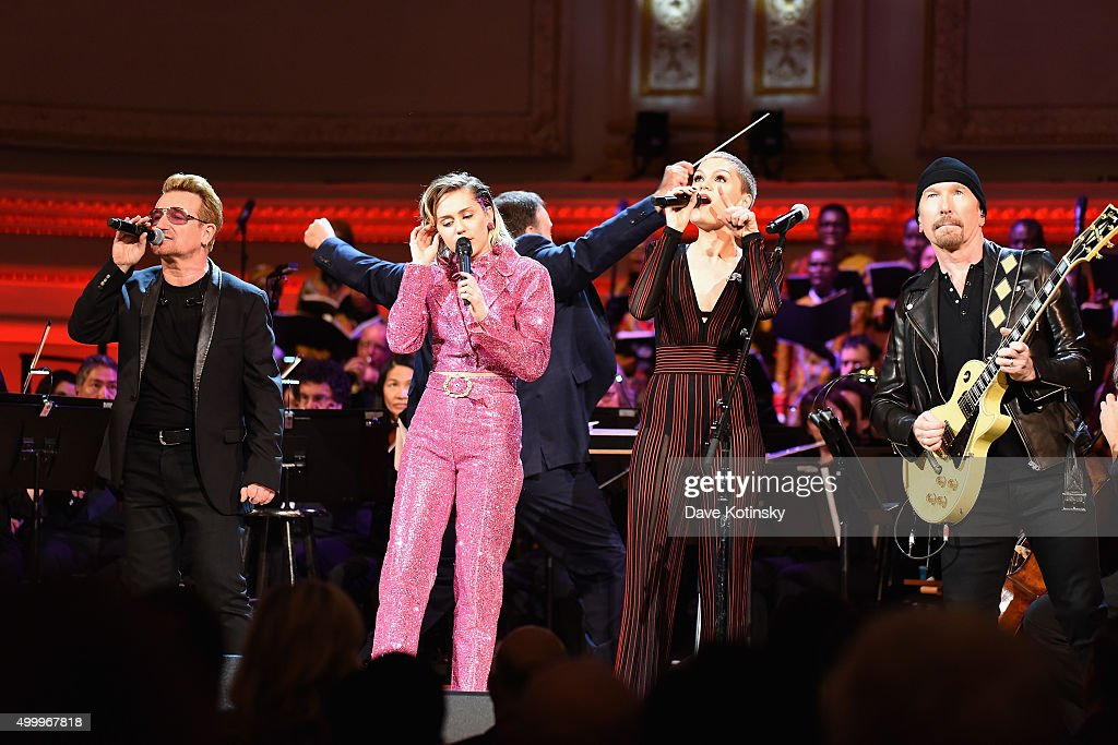 Musicians Bono, Miley Cyrus and Jessie J perform on stage during the ONE Campaign and (RED)s concert to mark World AIDS Day, celebrate the incredible progress thats been made in the fights against extreme poverty and HIV/AIDS, and to honor the extraordinary leaders, dedicated activists, and passionate partners who have made that progress possible. At Carnegie Hall on December 1, 2015 in New York City.