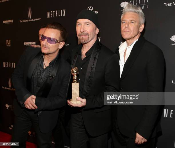 Musicians Bono The Edge and Adam Clayton of music group U2 pose with their Golden Globe for Best Original Song Motion Picture while they attend The...