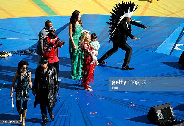 Musicians Carlos Santana Wyclef Jean Alexandre Pires Ivete Sangalo Shakira and her son Milan Pique and Carlinhos Brown on stage during the closing...