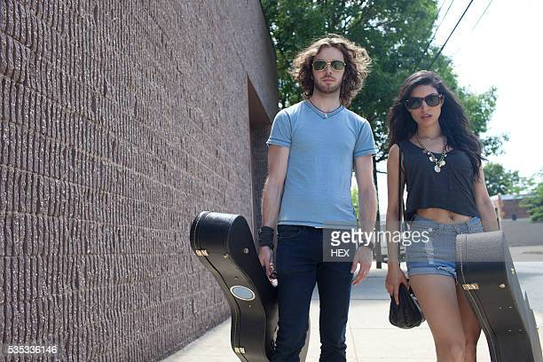musicians carrying guitar cases - guitar case stock pictures, royalty-free photos & images