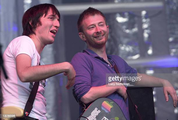 Musicians Colin Greenwood left and Thom Yorke from the band Radiohead joke as they perform onstage June 29 2001 at the Santa Barbara Bowl CA