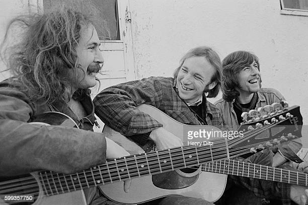 Musicians David Crosby Stephen Stills and Graham Nash play their guitars and relax on a porch
