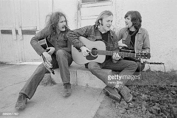 Musicians David Crosby Stephen Stills and Graham Nash sing and play their guitars on the porch