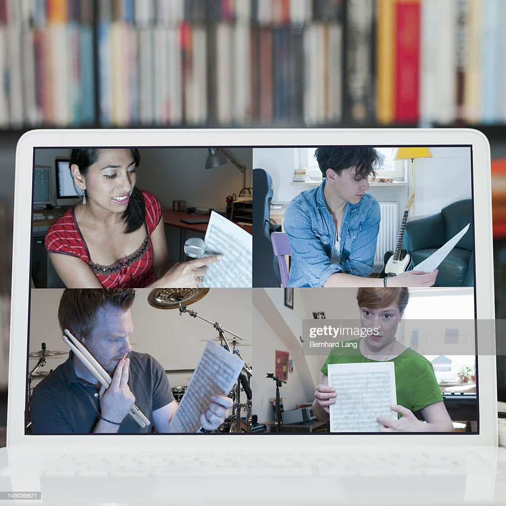 4 musicians discussing online, displayed on laptop : Stock Photo