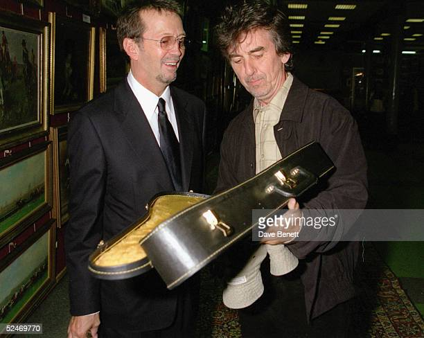 Musicians Eric Clapton and George Harrison view some of the guitars on offer at Christie's Auction on June 24 at Christie's The auction is to raise...