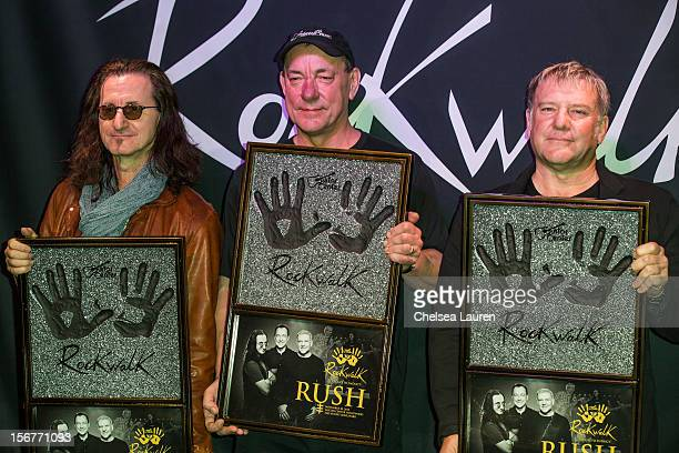 Musicians Geddy Lee Neil Peart and Alex Lifeson of Rush are inducted into Guitar Center's historic RockWalk at Guitar Center on November 20 2012 in...