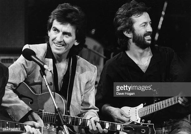 Musicians George Harrison and Eric Clapton performing on stage together as part of an all-star band for music legend Carl Perkins, October 23rd 1985.
