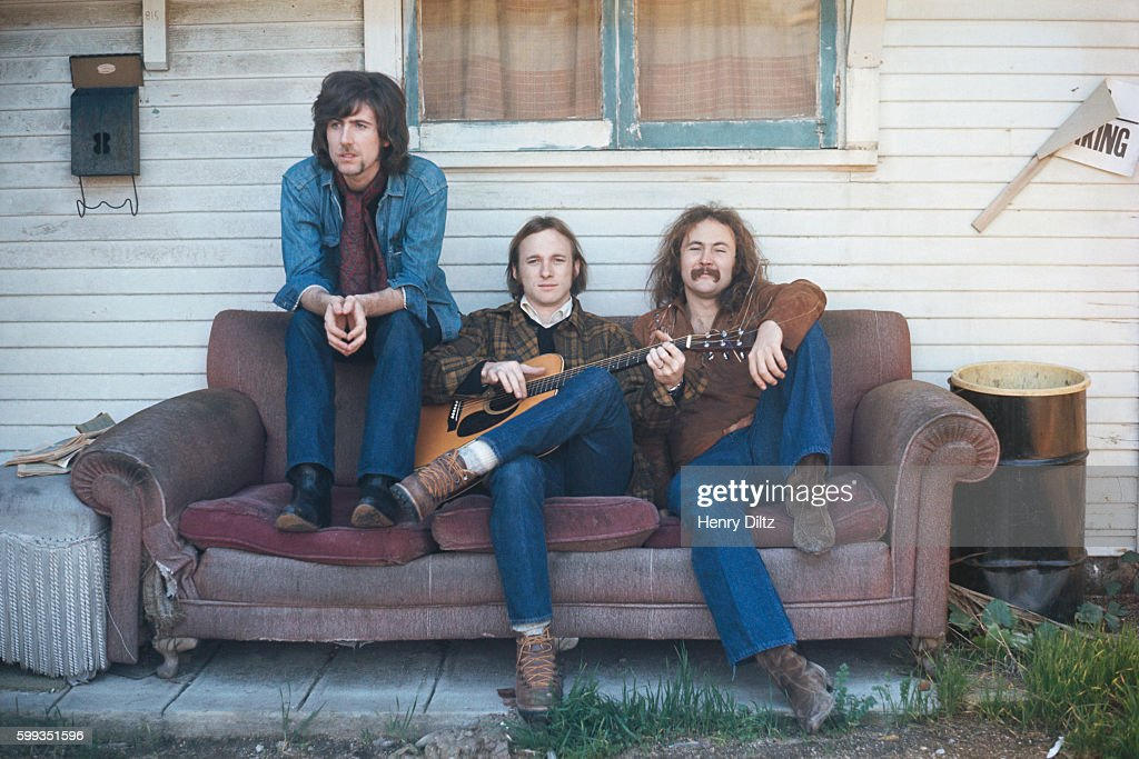 Musicians (from left) Graham Nash, Stephen Stills, and David Crosby sit together on an old torn sofa outside an old house. The rock group Crosby, Stills, and Nash were formed in the late sixties from members of The Hollies, The Byrds, and Buffalo Springfield. CSN collaborated with Neil Young occasionally, and racked up many hits in the sixties and seventies.