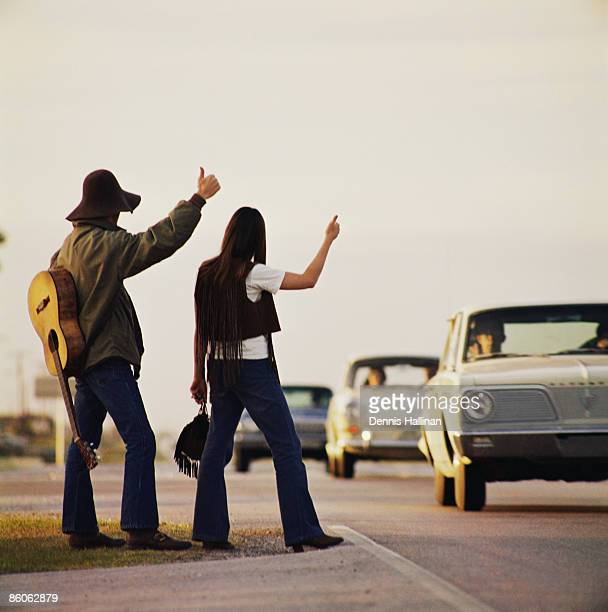 Musicians hitchhiking on highway