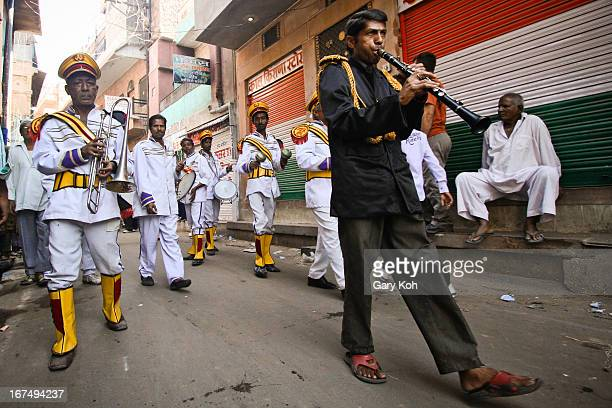 Musicians in colourful dress lead a wedding procession as it snakes through the back alleys of Jodhpur in the state of Rajasthan, India.