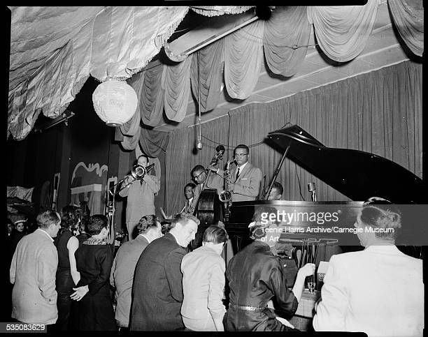 Musicians including Walt Harper on piano Nate Harper on saxophone bass and trombone performing on stage with scalloped curtains Pittsburgh...
