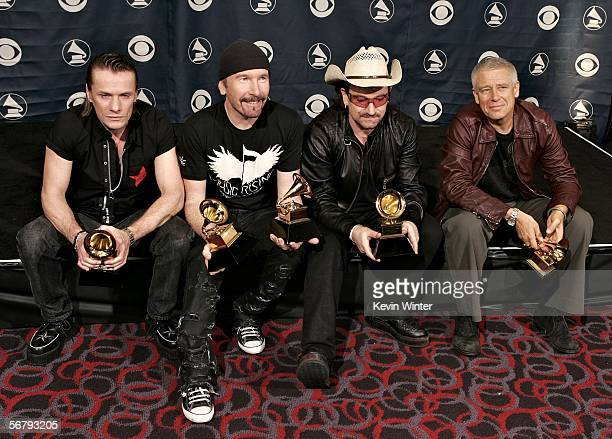 Musicians Larry Mullens Jr The Edge Adam Clayton and Bono of U2 pose with their award for Album of the Year in the press room at the 48th Annual...