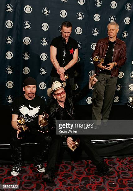 Musicians Larry Mullens Jr the Edge Adam Clayton and Bono pose with their Album of the Year award in the press room at the 48th Annual Grammy Awards...
