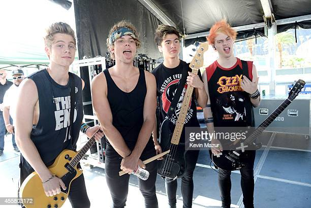 Musicians Luke Hemmings, Ashton Irwin, Calum Hood, and Michael Clifford of 5 Seconds of Summer pose onstage during the 2014 iHeartRadio Music...