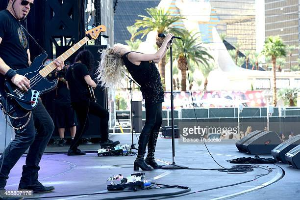 Musicians Mark Damon Ben Phillips and Taylor Momsen of The Pretty Reckless perform onstage during the 2014 iHeartRadio Music Festival Village on...