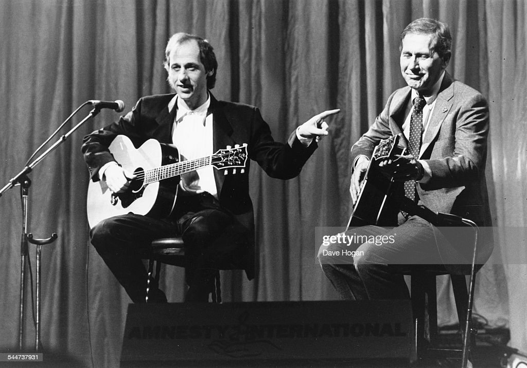 Musicians Mark Knopfler, of the band 'Dire Straits', and Chet Atkins, performing on stage at 'The Secret Policeman's Ball' at the London Palladium, March 1987.