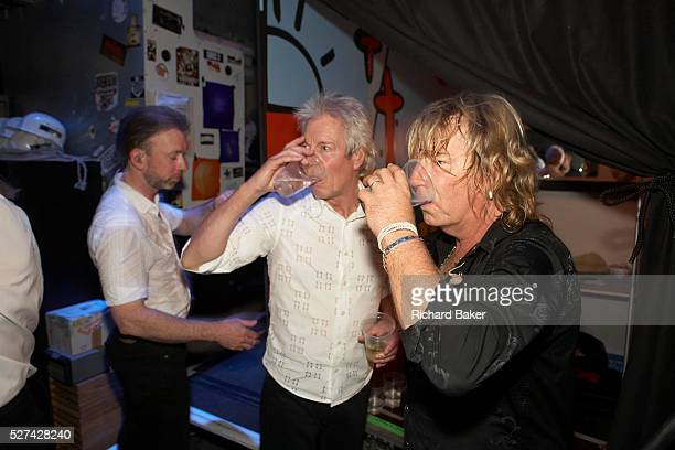 Musicians Matt Letley , Andy Bown and Rick Parfitt of the British rock band Status Quo come off stage before their encore to sip wine and water...
