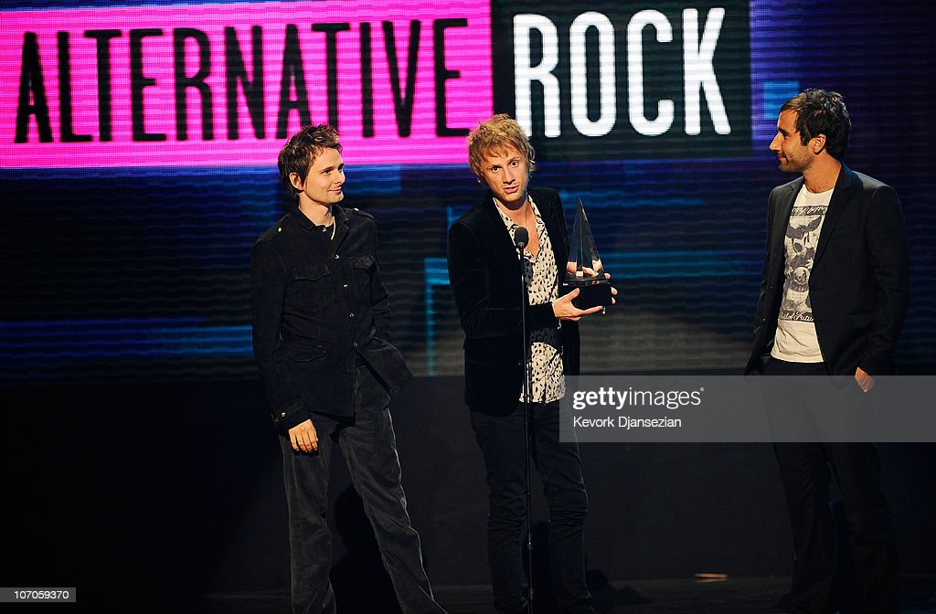 Musicians Matthew Bellamy (L) and Dominic Howard (C) of Muse accept the Alternative Rock Music - Favorite Artist award onstage during the 2010 American Music Awards held at Nokia Theatre L.A. Live on November 21, 2010 in Los Angeles, California.