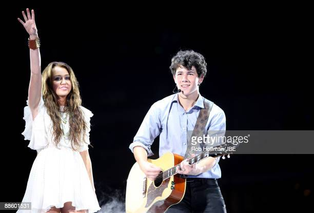 Musicians Miley Cyrus and Nick Jonas of Jonas Brothers perform at New Cowboys Stadium on June 20, 2009 in Dallas, Texas.
