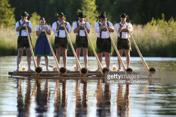Musicians of the alphorn band 'Holdersberger AlpTraumBläser' perform their skills on a raft floating on the Elbsee lake near Aitrang southern Germany...