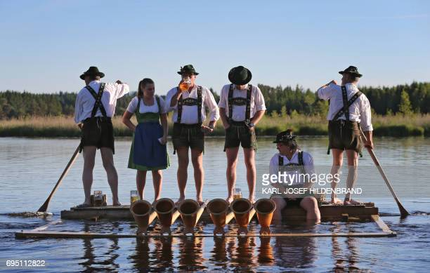 Musicians of the alphorn band 'Holdersberger AlpTraumBläser' stand on a raft floating on the Elbsee lake near Aitrang southern Germany on June 11...