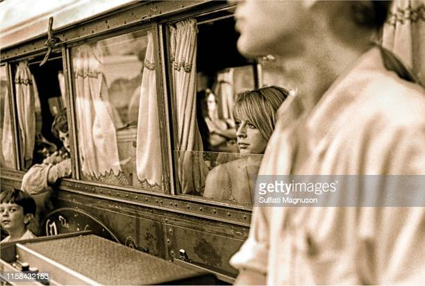 """Musicians peering out of the old train car """"dressing room"""": a blonde woman, two men; and a young boy looking at the camera at the 1st Elysian Park..."""