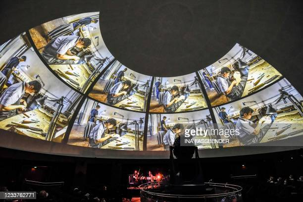 Musicians perform while photos by artist Heinrich Brinkmoeller-Becker on the crafting of violins in Cremona, Italy, are projected on the cupola of...