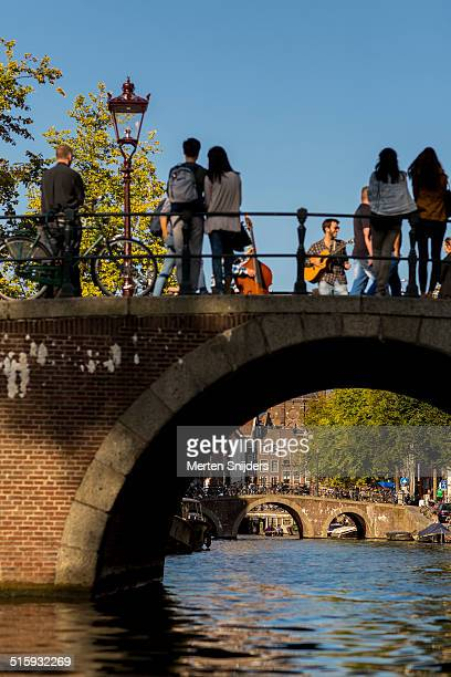 musicians performing on bridge - merten snijders stock pictures, royalty-free photos & images