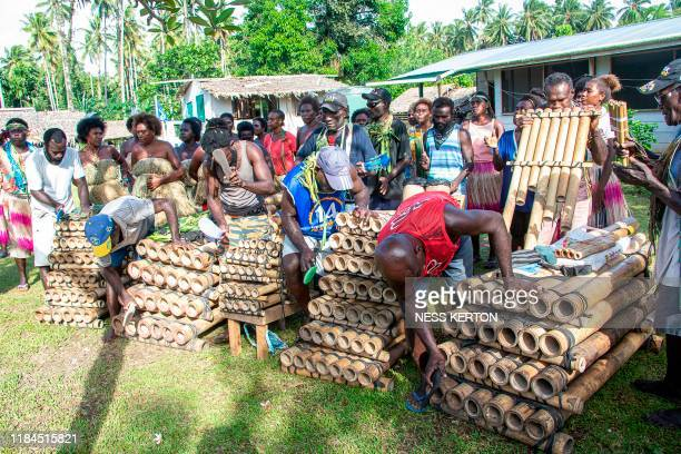 Musicians play bamboo pipes as people queue to vote at a polling station in the capital Buka in an historical independence vote on November 25 2019...