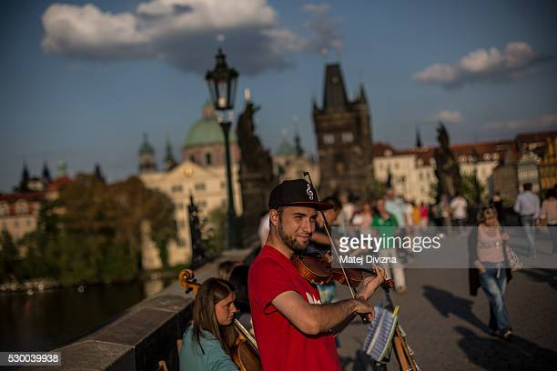 Musicians play on the Charles Bridge on May 9 2016 in Prague Czech Republic The Charles Bridge was begun to built in 1357 by Charles IV's builder...