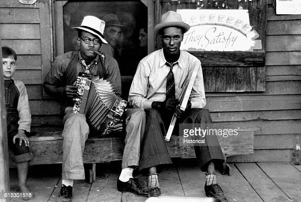 Musicians playing an accordion and a washboard in front of a store in New Iberia Louisiana Ca 19351945