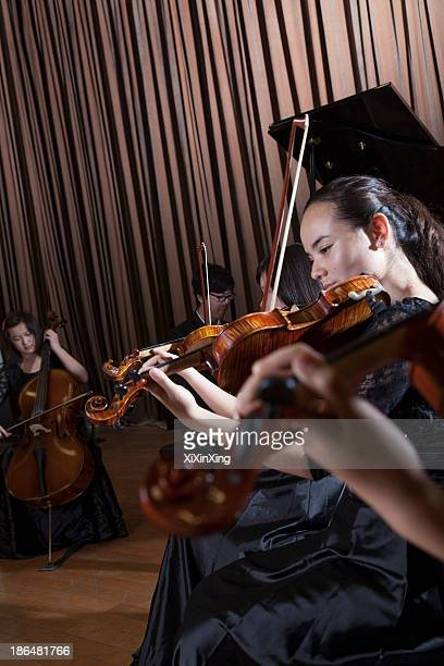 musicians playing during a performance, violinists at the front - pianist front stock pictures, royalty-free photos & images