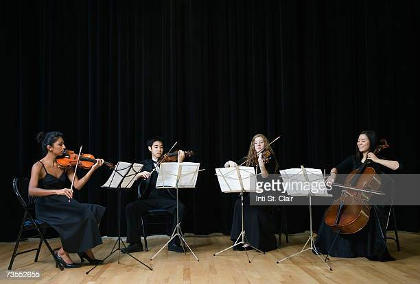 musicians playing guitar and cello on stage - vier personen stock-fotos und bilder