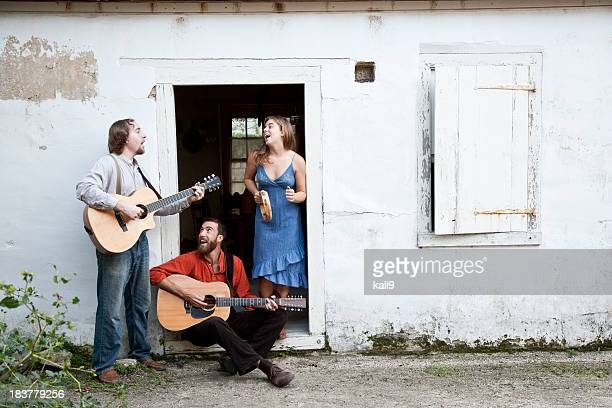 musicians playing in doorway of run-down building - countrymusik bildbanksfoton och bilder