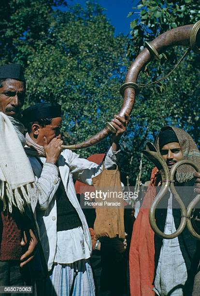 Musicians playing serpentine horns at a festival in India circa 1965